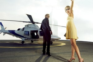 A wealthy man and woman getting on board a helicopter